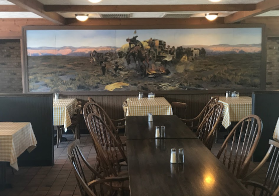 View of seating and western mural inside Strong City Restaurant