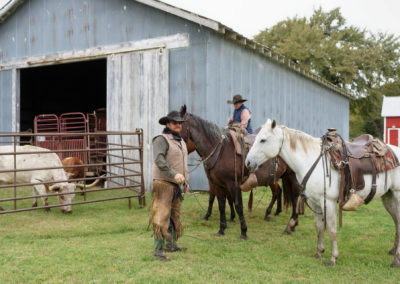 Members of the Hoy family with horses and a longhorn steer by the gray barn