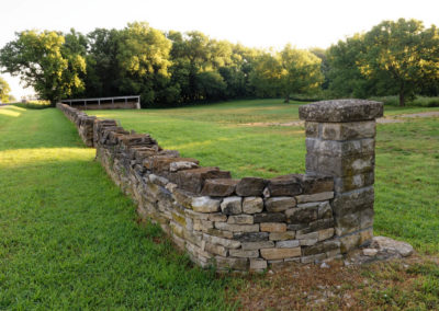 Curved section of stone fence by the front entrance