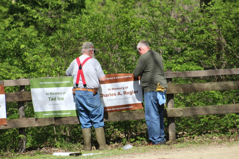 Volunteers hanging signs on wooden fence